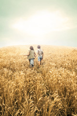 children running into wheat to the sunset