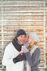 Composite image of happy couple in winter fashion holding mugs