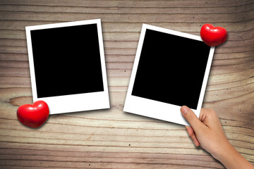 hand placing Blank valentine photo frames on wood background