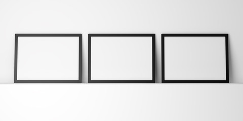 three blank black photo frames on white shelf
