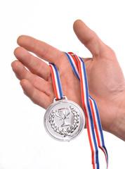 Vencedor celebrando triunfo sujetando medalla de plata.