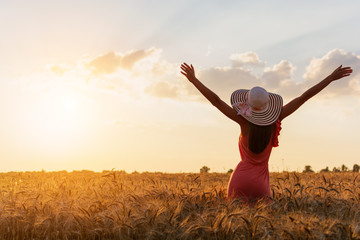 Beautiful rural girl on the wheat field on sunset