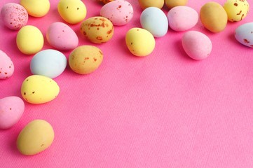 Chocolate candy Easter egg border on a pink paper background