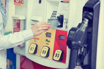 Woman hand swiping credit card at gas pump station
