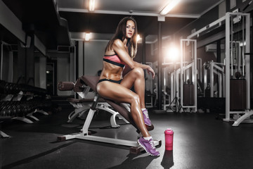 fitness girl with shaker posing on bench in the gym