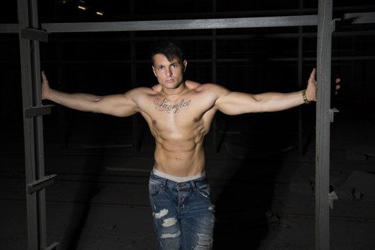 Muscular shirtless young man resting between metal bars