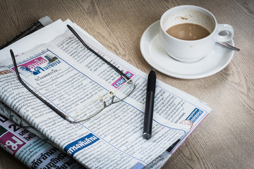 Newspaper, coffee and eyeglasses and pen