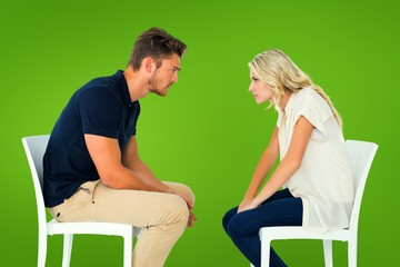 Composite image of young couple sitting in chairs arguing