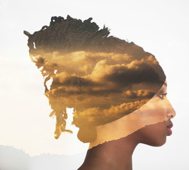 Double exposure of profile woman portrait and sunset clouds