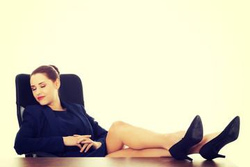Businesswoman sitting with legs on desk