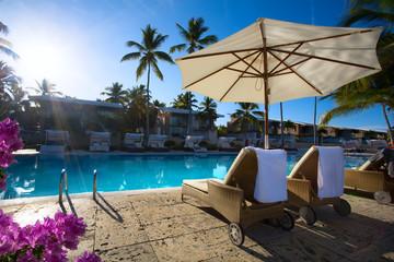 Fototapeta art Deckchairs in tropical resort hotel pool