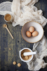 eggs on bowl, cane sugar and crumbled biscuits