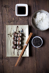 overhead shot of hosomaki sushi on plate with soy sauce