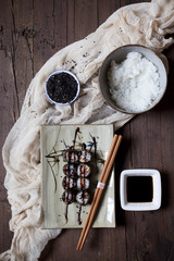 hosomaki sushi on plate with soy sauce and bowl of rice