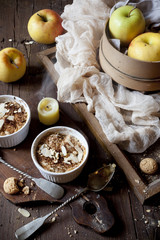 two portions of apple crumble with almonds on wooden table