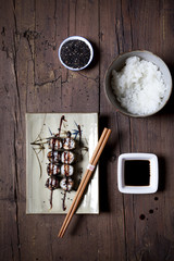 overhead shot of hosomaki sushi on plate with soy sauce and rice