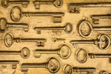 Different antique keys on a wooden background