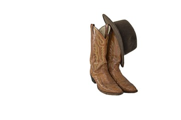 A pair of fancy brown cowboy boots with a brown outback hat