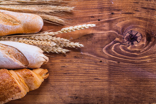 baguettes and croissant with wheat ears on old wooden board
