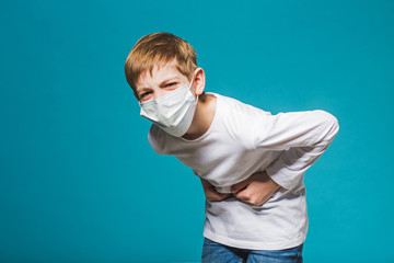 Boy wearing protection mask having stomach ache