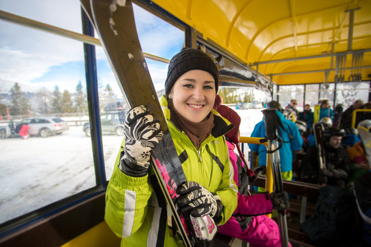 portrait of smiling woman riding in bus with skis