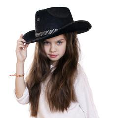 Portrait of a beautiful little girl in a black cowboy hat