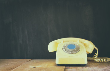 Retro telephone on wooden table. filtered image with faded retro