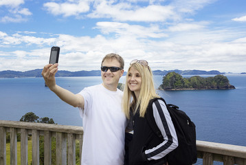Couple on vacation taking photo of beautiful ocean view