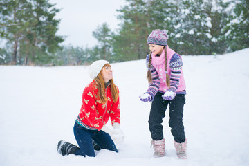 girl and mother playing with snow