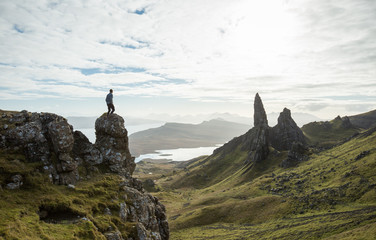 Man standing on mountain rock above Scottish Highlands