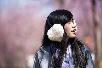 Happy woman traveler with sakura tree on vacation in Japan
