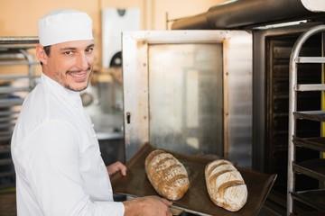Happy baker holding tray of fresh bread