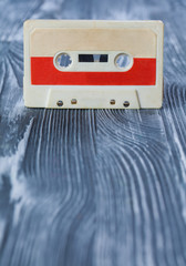 red audio cassette on the gray wooden background.