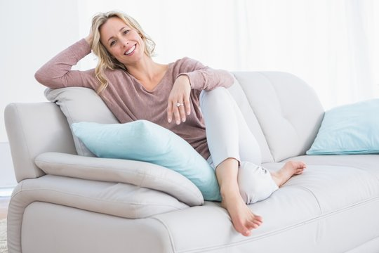 Pretty blonde relaxing and sitting on couch