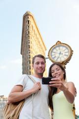 New York couple taking tourist selfie Flatiron NYC