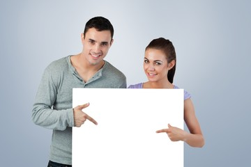 Young couple pointing at banner they are holding