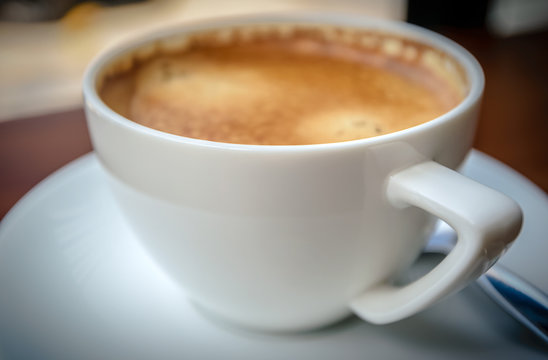 part of front coffee frothy  Brown in white coffee Cup