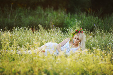 girl in a white sundress and a wreath of flowers on her head sit