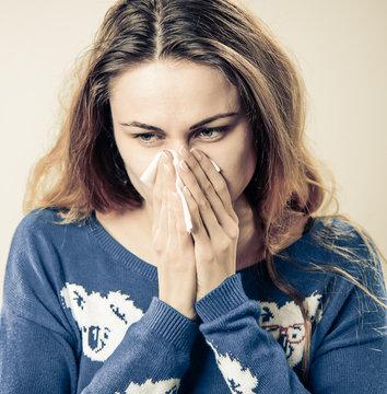 woman blowing nose through napkin