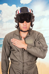 young handsome pilot wearing uniform and helmet over beach