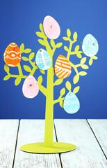 Felt Easter eggs on decorative tree  on colorful background