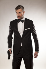 handsome man in a suit with a gun in his hand