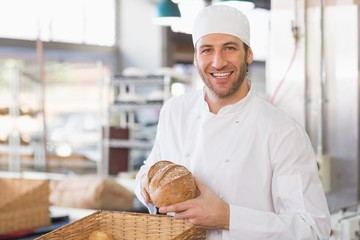 Happy baker with loaf of bread