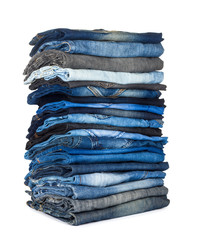 high stack of blue jeans and black on a white background