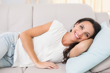 Pretty brunette lying on couch