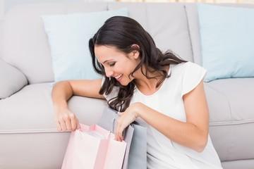 Pretty brunette opening shopping bag