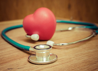 Red heart and stethoscope on wooden background.