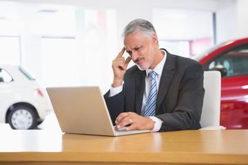 Upset businessman working on computer