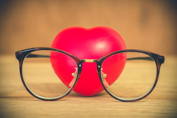 Heart of love wearing glasses on wooden