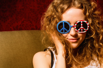 Young girl with curly hair wearing sunglasses with the American